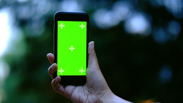 vídeos de stock e filmes b-roll de chroma key : mobile phone on hand - jardim particular
