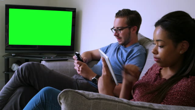 Chroma key tv, surfing the net. Couple at home.