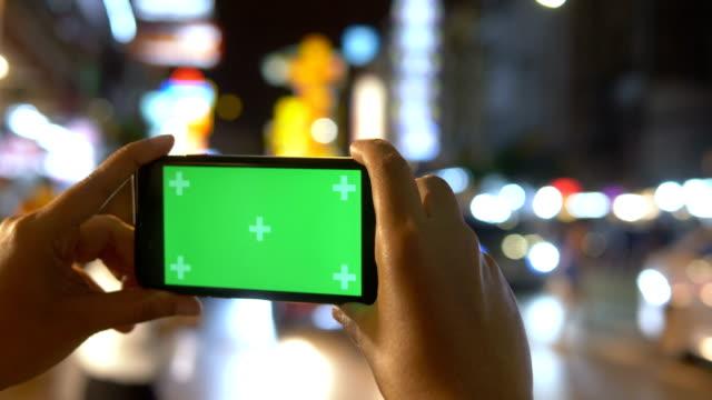 chroma-key: frauen halten smartphone über nacht stadt - photographing stock-videos und b-roll-filmmaterial