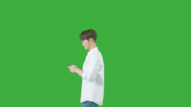 chroma key - young man walking and using his smart phone - in front of stock videos & royalty-free footage