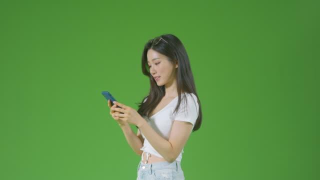 chroma key - young woman taking selfie with smartphone and using smartphone - profil sedd från sidan bildbanksvideor och videomaterial från bakom kulisserna