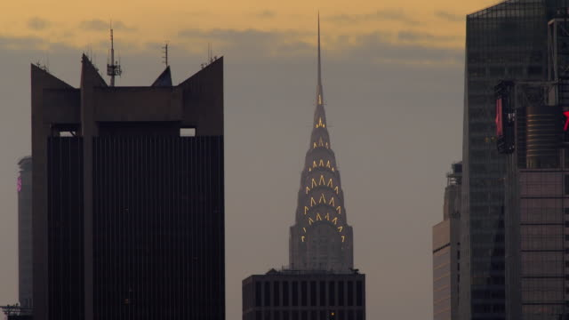 chrysler building lights turn off in the early morning hours against a clear sky. - chrysler building stock videos & royalty-free footage