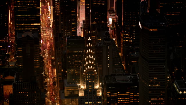 aerial chrysler building lit by lights at night - chrysler building stock-videos und b-roll-filmmaterial