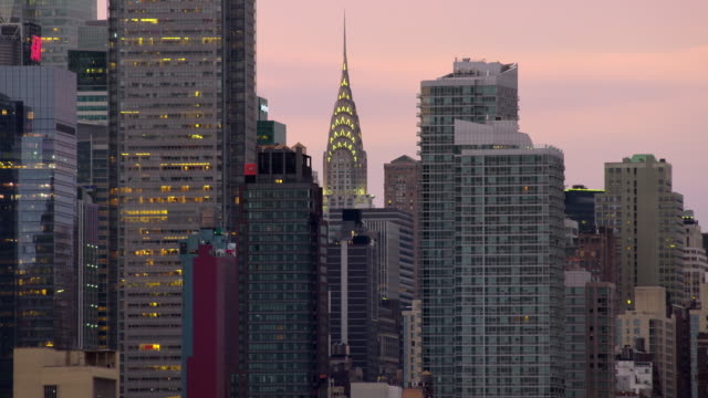 Chrysler Building surrounded by other New York City skyscrapers lit up in the early evening.