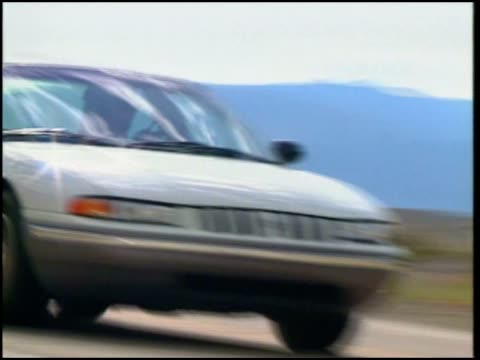 stockvideo's en b-roll-footage met a chrysler concorde driving on a desert road - chrysler