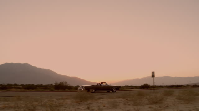 vidéos et rushes de ws pan chrysler imperial 1964 convertible driving on desert road at sunset - route 66