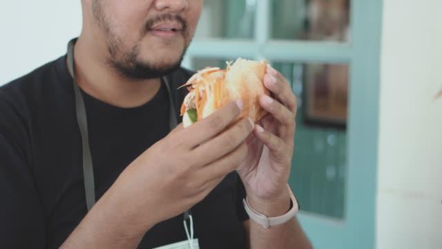 vidéos et rushes de homme asiatique barbu de chubby mordant le sandwich vietnamien banh mi - moustache