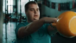 Chubby man doing exercise with kettlebell