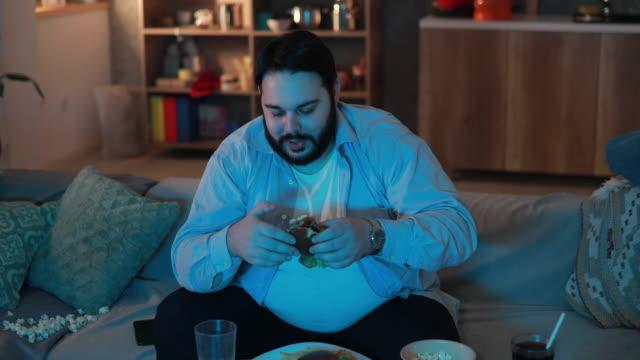 vídeos de stock, filmes e b-roll de hambúrguer homem gordinho comendo - programa de televisão