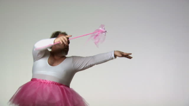 Chubby man in tutu ballet dancing with a wand