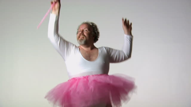 Chubby man in tutu ballet dancing with wand