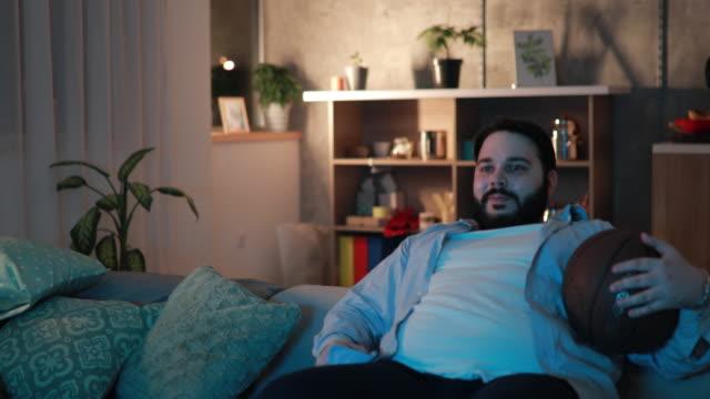 chubby man watching a basketball match - poltrona video stock e b–roll