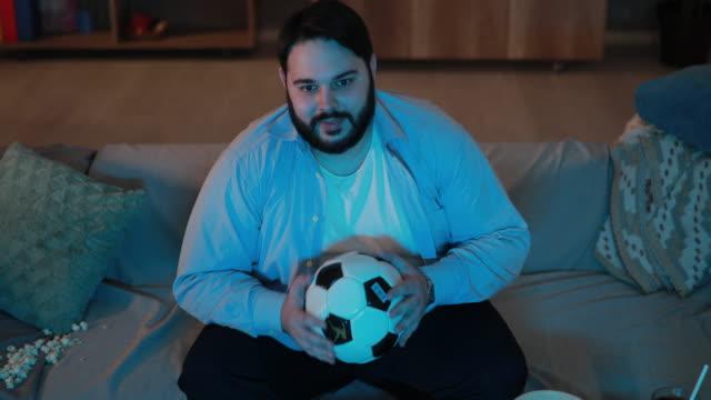 uomo paffuto che guarda una partita di calcio - messy video stock e b–roll