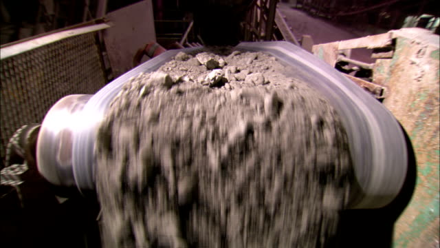 stockvideo's en b-roll-footage met chunks of aggregate drop from a conveyor into a pit at a brick plant. - schalie