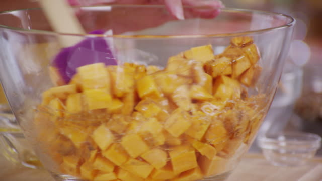 Chunks of cheddar cheese are covered with honey and stirred in a glass bowl.