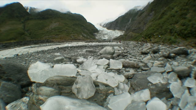 stockvideo's en b-roll-footage met ws chunks of glacial ice with glacier in background / franz josef glacier, new zealand - groothoek