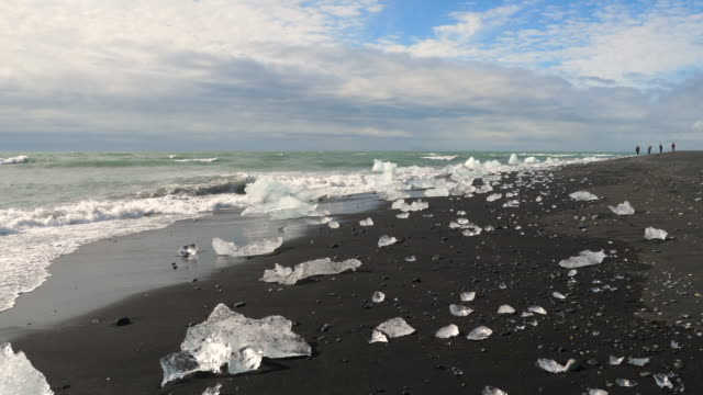 chunks of ice on the water line in the black beach near jökulsárlón glacial lake, iceland. - nordatlantik stock-videos und b-roll-filmmaterial