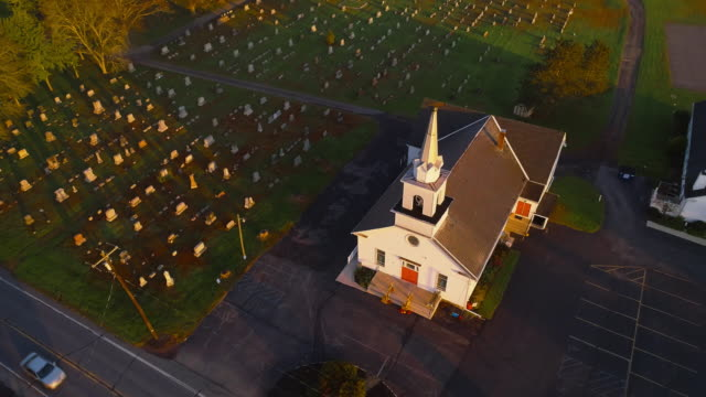 church and cemetery at sunrise. brodheadsville, poconos region, pennsylvania. aerial drone video with the forward and tilting-down camera motion. - scena rurale video stock e b–roll