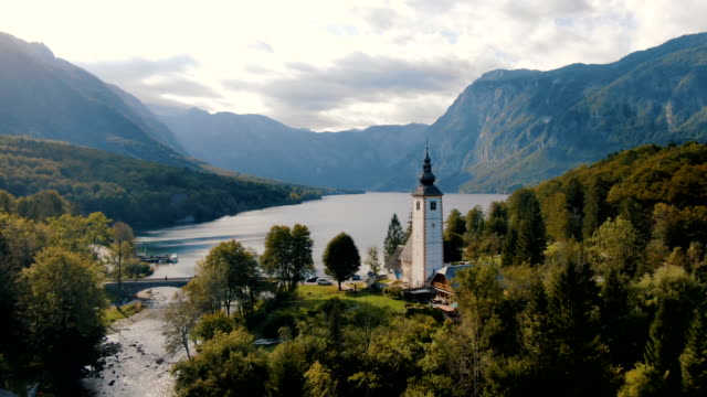 stockvideo's en b-roll-footage met church and lake in background , lake bohinj / aerial drone view - slovenië