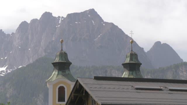 church and mountain backdrop in the town of st. johann, austrian alps, tyrol, austria, europe - 北チロル点の映像素材/bロール