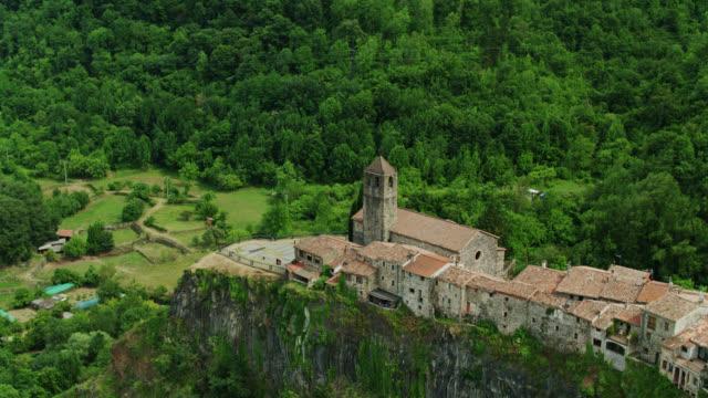 chiesa e vecchie case in pietra, castellfollit de la roca - colpo di drone - roca video stock e b–roll