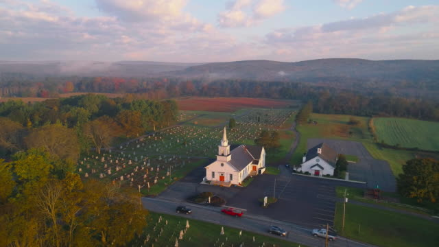 日の出の教会。ブロッドヘッドズビル、ポコノス地域、ペンシルベニア州。国道209号線の朝の交通。静止カメラで空中ドローンビデオ。 - プロテスタント点の映像素材/bロール