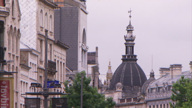 a church dome and spire dominate a skyline in antwerp. - spire stock videos & royalty-free footage