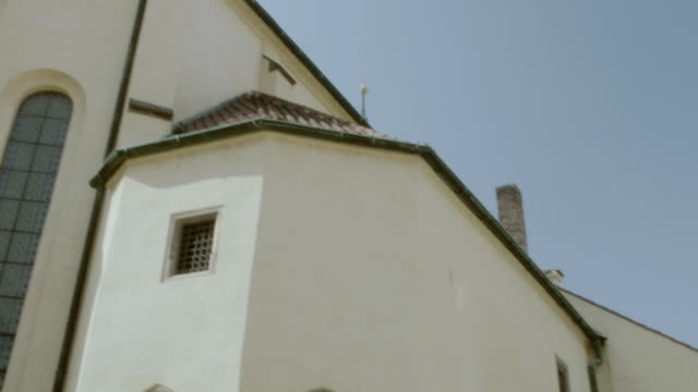 tu church exterior with arched doorways, steeply sloping roof, and steeple - steeple stock videos & royalty-free footage