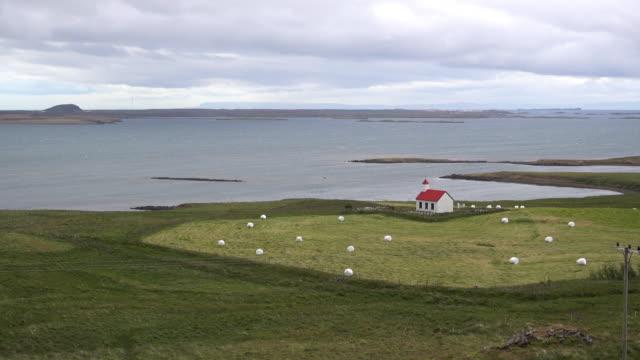 church in a wide open landscape near an arctic fjord - snäfellsnes stock-videos und b-roll-filmmaterial