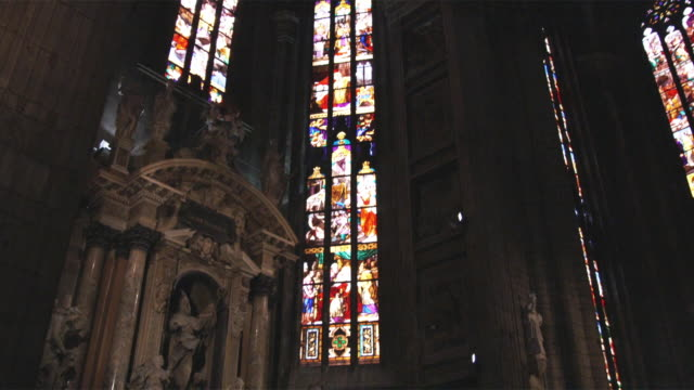 ws tu church interior with sculptures and stained glass / milan, italy - ambientazione interna video stock e b–roll