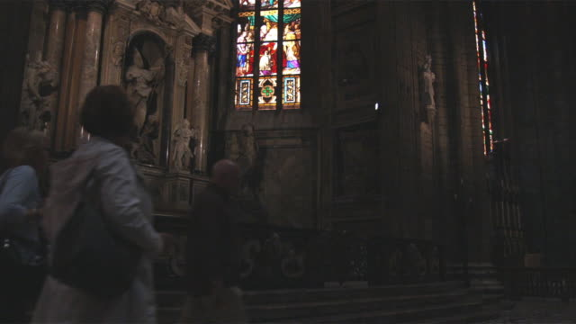 stockvideo's en b-roll-footage met ms church interior with stained glass and people passing / milan, italy - man met een groep vrouwen
