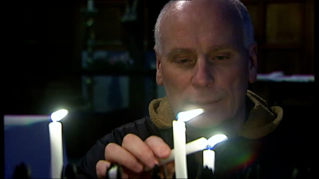 church of england launch text service during lent; england: london: int reporter lighting candle inside church three lit candles reporter along in... - 四旬節点の映像素材/bロール
