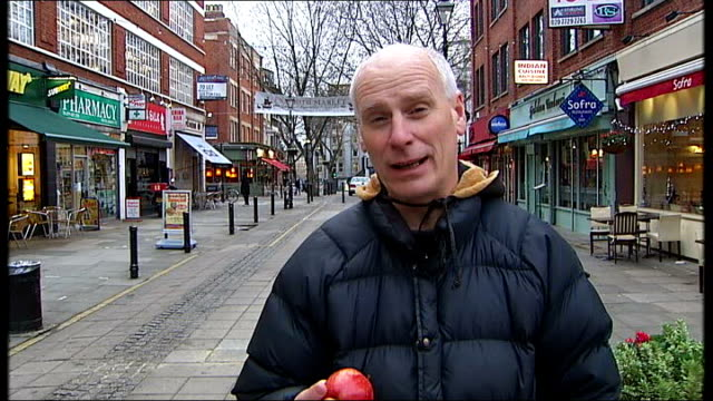 church of england launch text service during lent; reporter to camera handing apple to cameraman - 四旬節点の映像素材/bロール