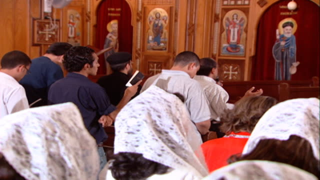 church of st. george. mls rear on worshippers praying and reciting from prayer books during mass. - 信者点の映像素材/bロール