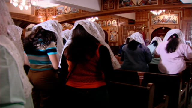 church of st. george. rear female coptic worshippers inside a church with their heads covered in white lace scarves. - credente video stock e b–roll
