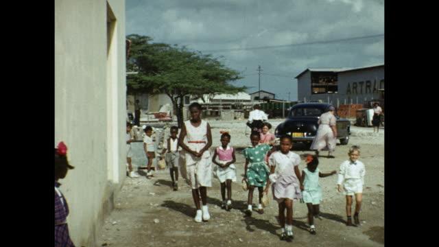 vídeos y material grabado en eventos de stock de 1954 home movie church patrons getting off bus and milling around parking lot / aruba, lesser antilles  - antillas occidentales