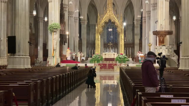 church pews stand empty as cardinal timothy dolan, the archbishop of new york, celebrates easter sunday mass in a nearly empty st. patrick's... - easter stock videos & royalty-free footage