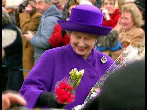 Church service/ Queen's Christmas message EXT Sandringham CMS Queen along collecting flowers from crowd R followed by Prince Philip Andrew Edward