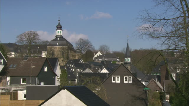 a church steeple dominates the skyline of a quaint german village. - steeple stock videos & royalty-free footage
