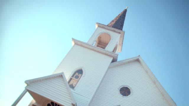 a church steeple rises into a hazy blue sky. - steeple stock videos & royalty-free footage