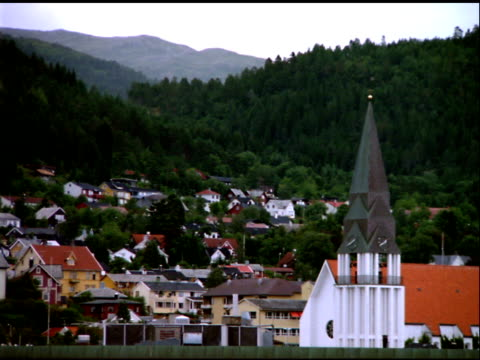 church steeple with town rising up tree covered hills in background, norway - steeple stock videos & royalty-free footage