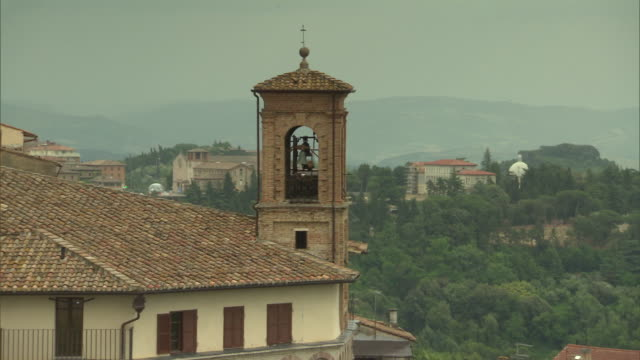 church tower w/ statue inside other buildings tree covered hills in perugia city valley bg - ペルージャ市点の映像素材/bロール