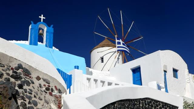 church, windmill and greek flag, santorini, greece  - griechische flagge stock-videos und b-roll-filmmaterial
