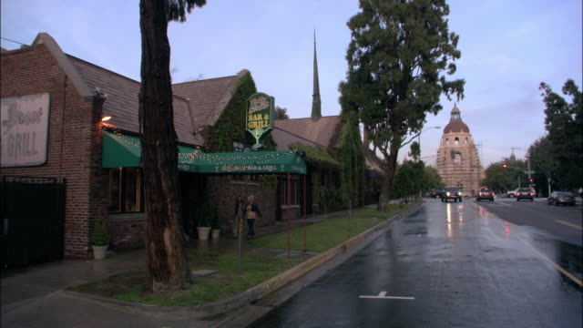 WS Church with large steeple at the end of street; pedestrians walking past front and cars driving past of Holly street Bar and Grill on a rainy day / Pasadena, California, United States