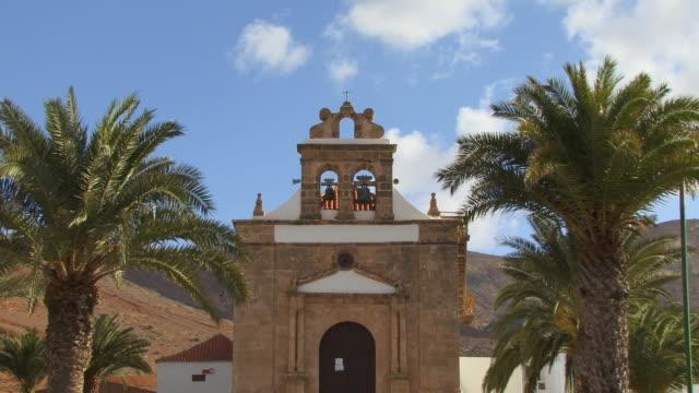 ms, zo, church with palm trees in foreground / vega de rio palmas, fuerteventura, canary islands, spain - solfjäderspalm bildbanksvideor och videomaterial från bakom kulisserna
