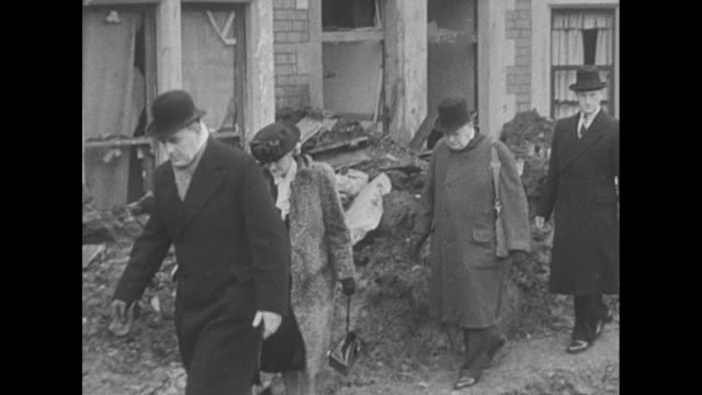 Churchill and wife Lady Churchill walk through rubble / Churchill stops and talks to woman on bombedout street / he stops and talks to man amid...