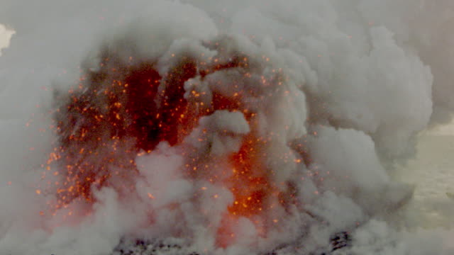 Churning white smoke with explosions of fiery red lava / Kilauea volcano, Hawaii