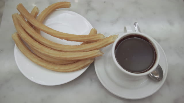 churro and chocolate cup typical in spain - churro stock videos & royalty-free footage
