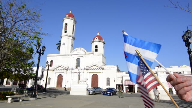 vidéos et rushes de cienfuegos cuba main square and parish church twin tower cathedral with usa and cuban flags flying for unity now - clocher élément architectural