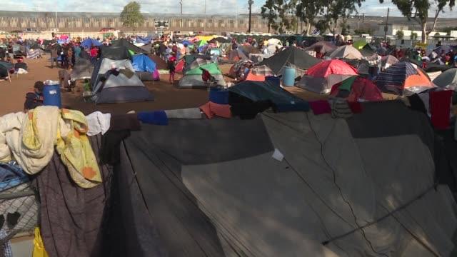 vídeos y material grabado en eventos de stock de cientos de centroamericanos de la caravana migrante amanecieron el viernes en un nuevo campamento instalado junto a un paso fronterizo de la mexicana... - ee.uu